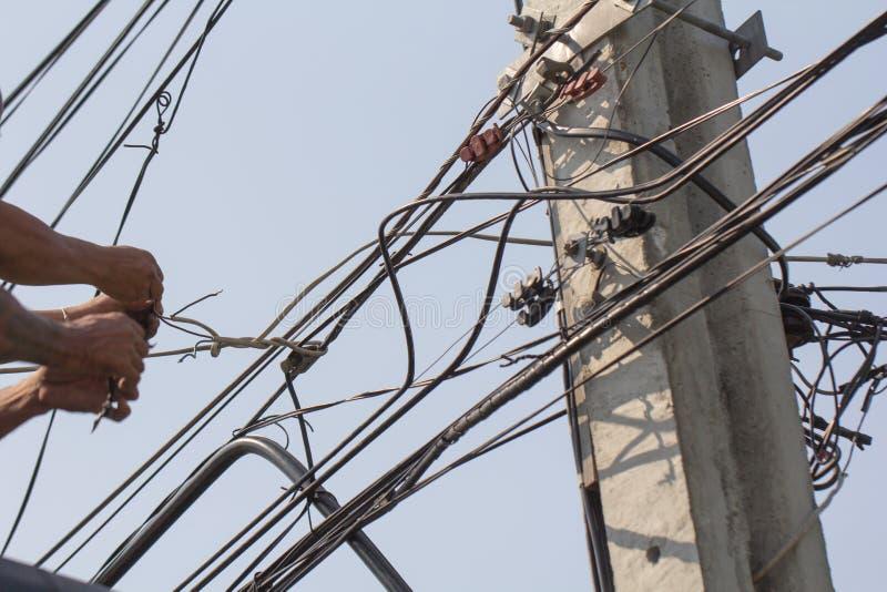 Elektrisk maintenancearbetar för att reparera elektriska linjer Tilltrasslade elektriska Cablessomarbetar på på hög nivå arkivfoton