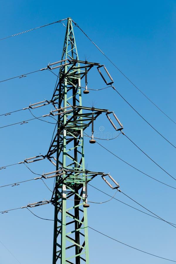 Elektrisk mast i gr?n f?rg med isolatorn och kablar royaltyfri foto