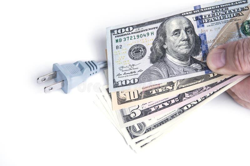 Elektrisk propp med dollarpengar på viten Energiräddningbegrepp royaltyfria foton