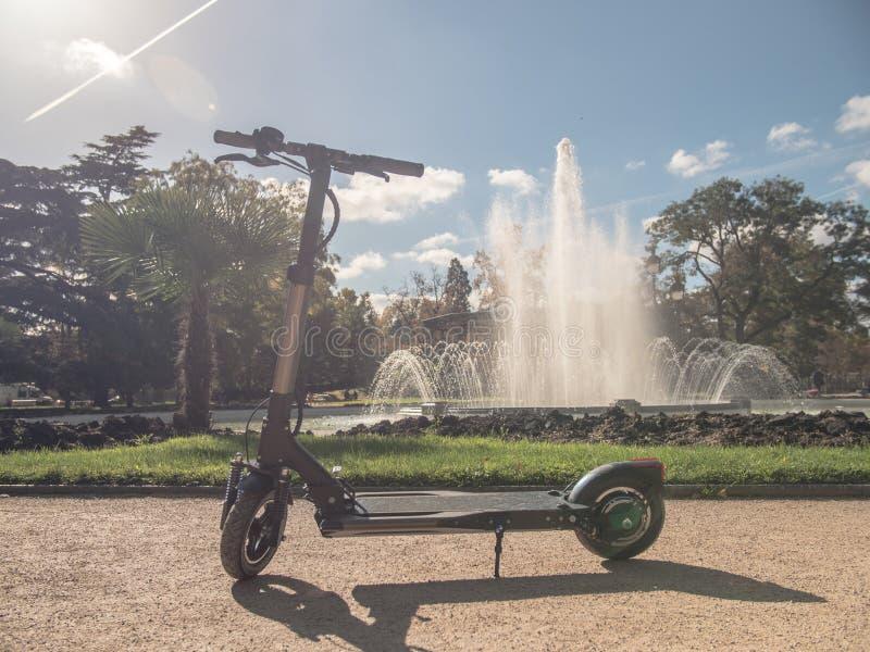Elektrisk sparkcykel i Sunny Park med springbrunn 2 arkivbilder