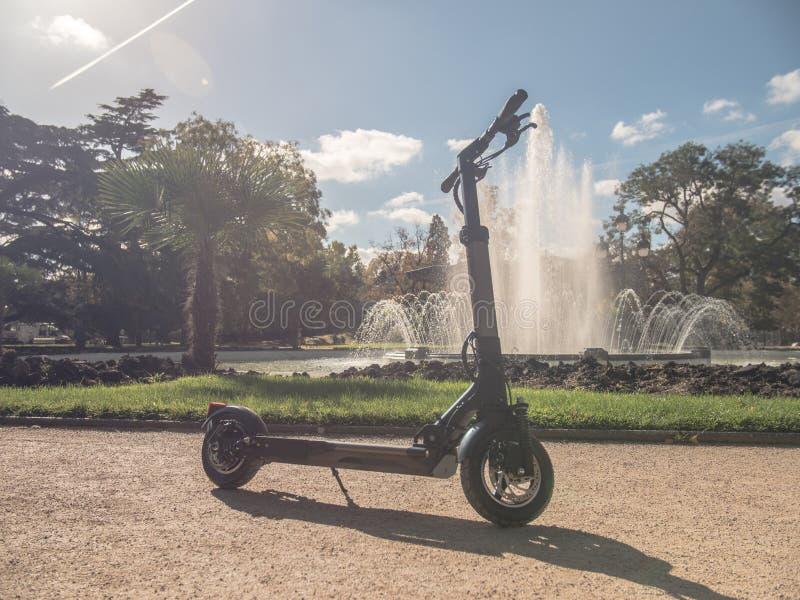 Elektrisk sparkcykel i Sunny Park med springbrunnen arkivbild
