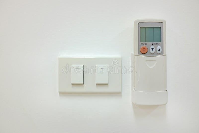 Elektrisk strömbrytare- och luftkonditioneringsapparatfjärrkontroll på den vita väggen royaltyfria foton