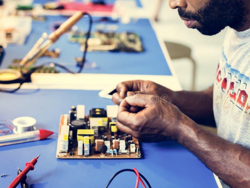 Elektrisk tekniker som arbetar på elektroniskt bräde royaltyfria bilder
