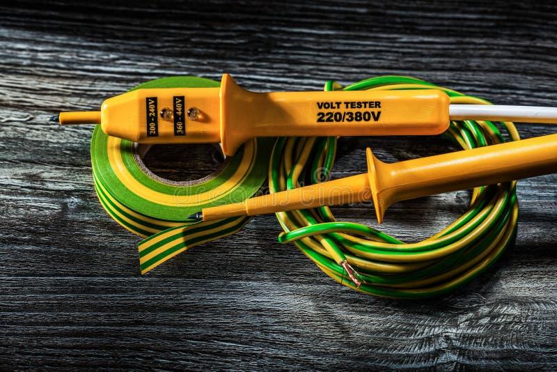 Elektrisk testersnygg man av det rullande kabelelektrikerbandet på trä royaltyfri bild