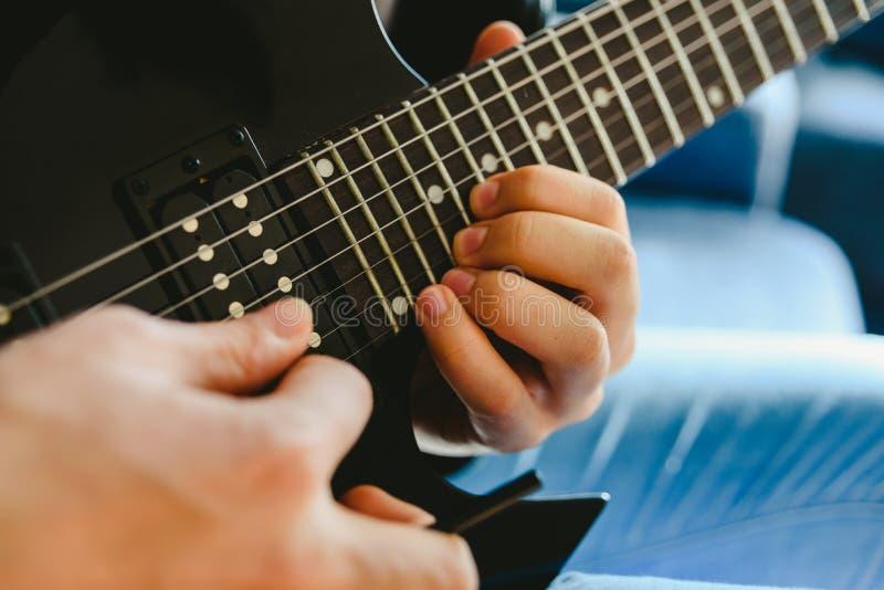 Elektriska gitarrer som undervisar hur man placerar fingrar för att spela en sladd arkivbild