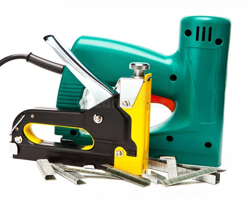 Elektriska häftapparater och manuellt mekaniskt - för reparationsarbete i huset och på möblemang på en vit bakgrund fotografering för bildbyråer