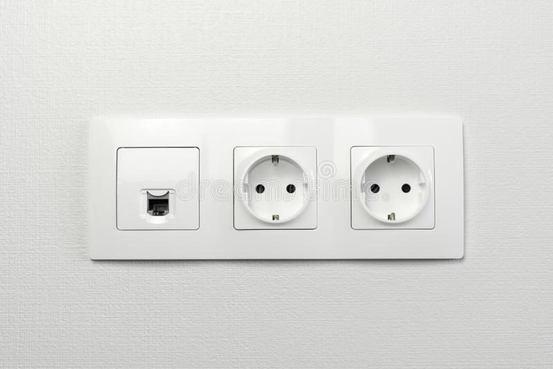 Elektriska håligheter på väggen med den svarta anslutningsinternetproppen och vit tråd Hålighetuppsättning med usb-kabel och elek royaltyfria bilder