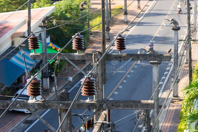 Elektriska isolatorer och trådar på poler i Thailand royaltyfria bilder