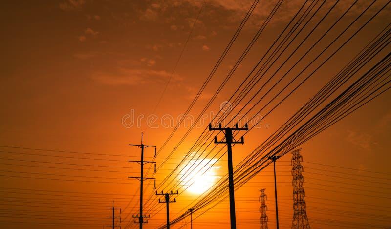 Elektriska pol- och överföringslinjer för hög spänning på solnedgångtid med orange och röd himmel och moln arkitektur silhouette royaltyfria foton