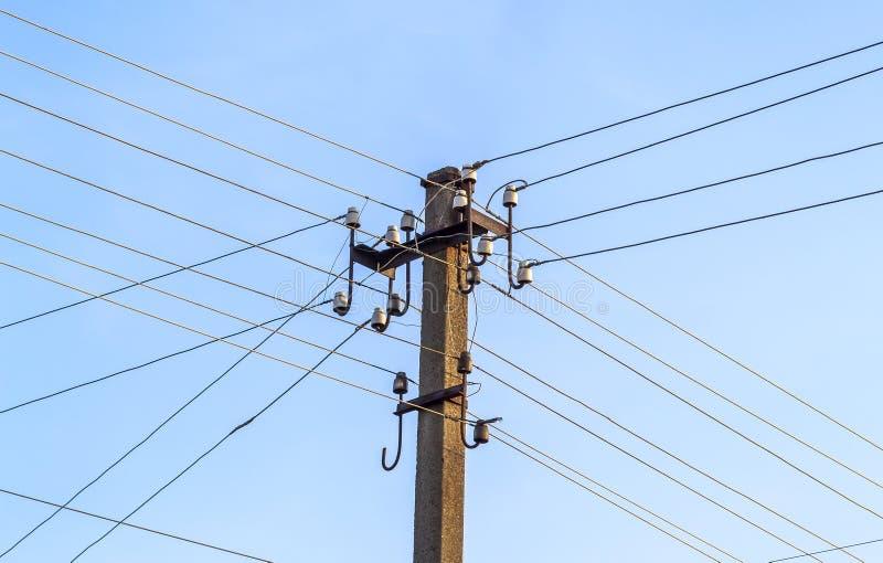 Elektriska polkraftledningar och trådar med blå himmel arkivfoton