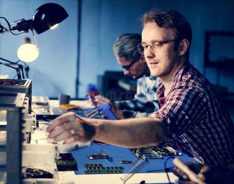 Elektriska tekniker som arbetar på elektronikdelar arkivfoto