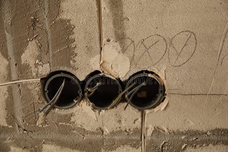 Elektriskt hålighethål på betongväggen Under den elektriska håligheten för konstruktion royaltyfri foto