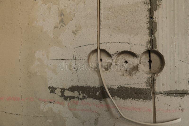 Elektriskt hålighethål på betongväggen Under den elektriska håligheten för konstruktion royaltyfri bild