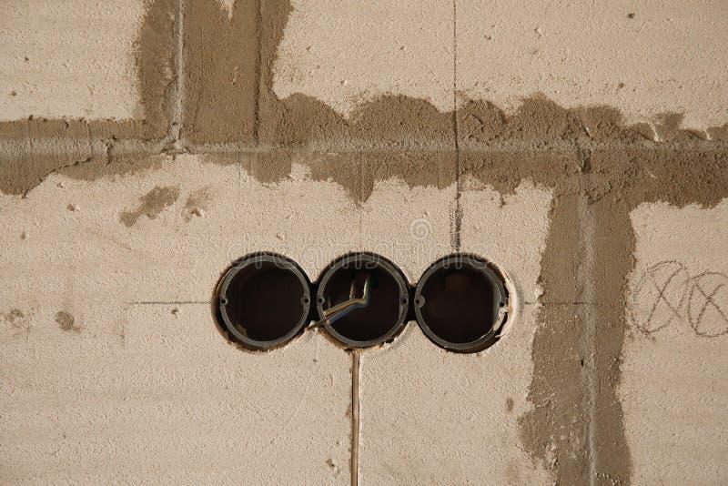 Elektriskt hålighethål på betongväggen Under den elektriska håligheten för konstruktion royaltyfri fotografi