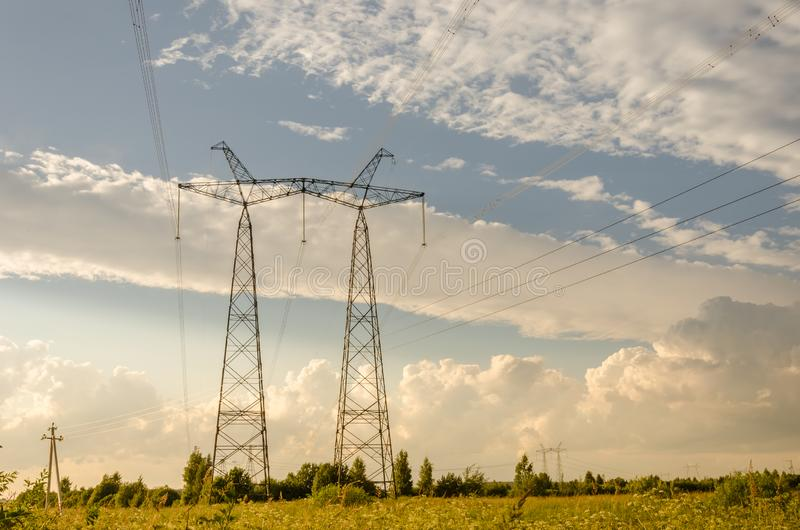 Elektriskt högt spänningstorn/kraftledningstolpe mot den blåa himlen royaltyfri bild