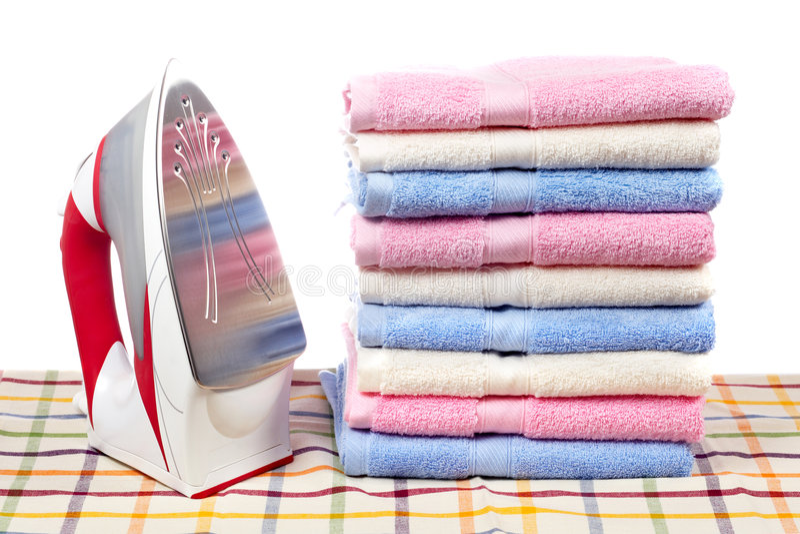 elektriskt järn staplade handdukar arkivfoto