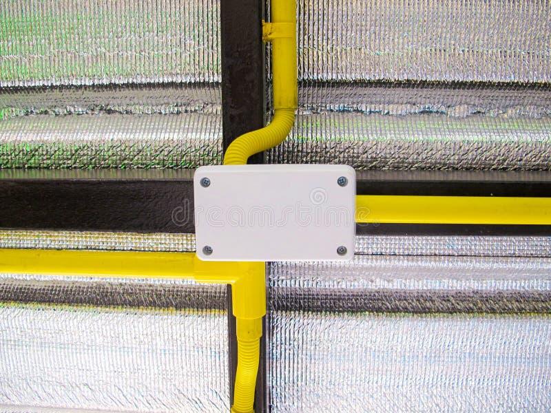 Elektriskt ledningsnät i gult rör arkivfoton