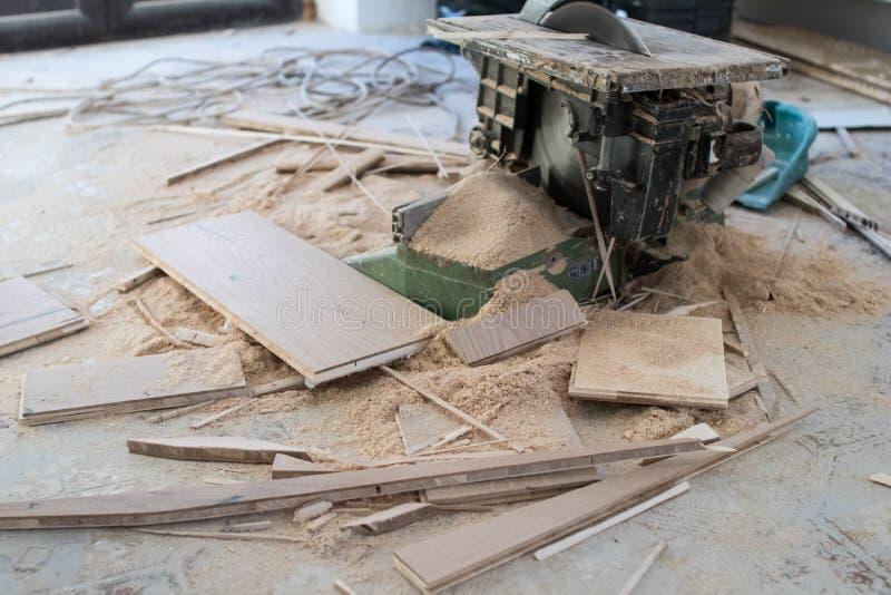 Elektriskt såg för bitande parkettbräden under renoveringen av arkivfoto