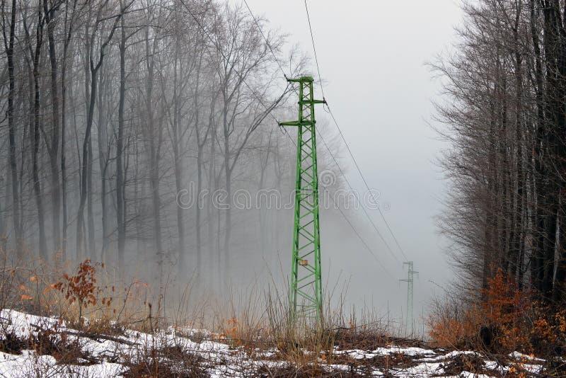 Elektriskt torn i en dimmig skog arkivfoton