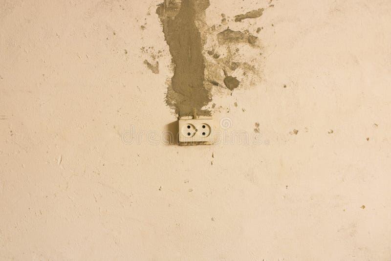 Elektriskt uttag p? den gamla betongv?ggen Isolerat p? ljus bakgrund arkivfoton