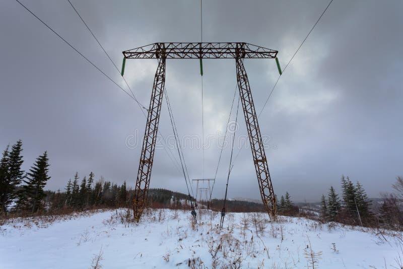 ElektrizitätsübertragungsStromleitungen auf Winterhintergrund Hochspannung ragen hoch Metallelektrizitätsübertragungsmast stockfoto