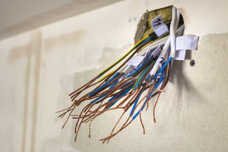 Elektro blootgestelde verbonden draden die van contactdoos op witte muur uitpuilen Elektro bedradingsinstallatie Het eindigen de  stock foto's
