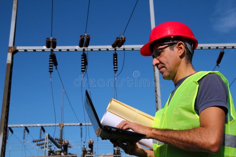 Elektro Ingenieur met Laptop en Blauwdrukken stock foto