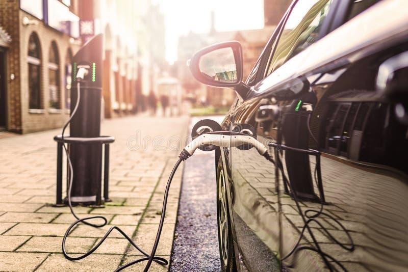 Elektro-Mobil, das auf Straße, in Großbritannien auflädt lizenzfreies stockbild
