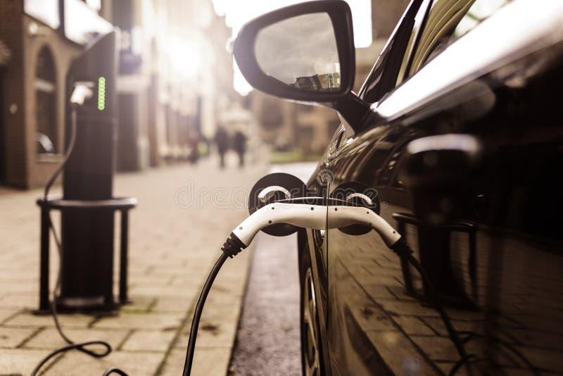 Elektro-Mobil, das auf Straße, in Großbritannien auflädt stockfotos