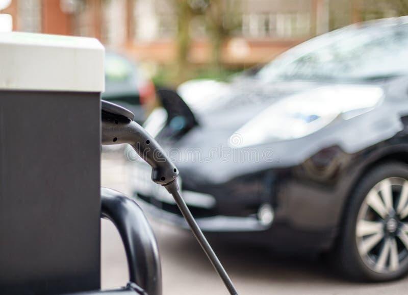 Elektro-Mobil, das auf Straße, in Großbritannien auflädt stockbild