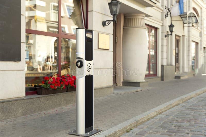 Elektro-Mobil, das Ev-Station mit Stecker der Stromkabelversorgung für Ev-Auto auflädt Elektrisches Eco-Autoladegerät in der Stad lizenzfreies stockfoto