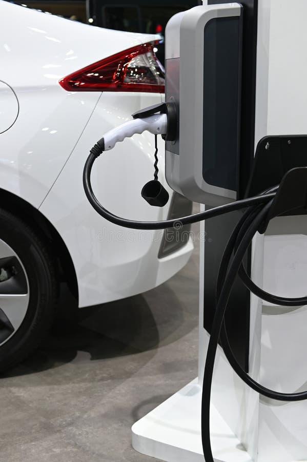 Elektroauto, das auf Parkplatz mit Ladestation des elektrischen Stromversorgungsautos auf Stadtstraße auflädt stockbild