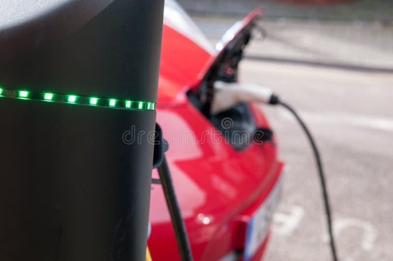 Elektroauto, das auflädt, um an der Straßenrandstromversorgung wieder zu tanken stockbild