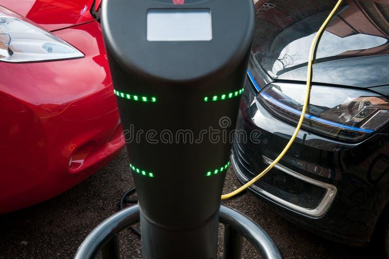 Elektroauto, das auflädt, um an der Straßenrandstromversorgung wieder zu tanken stockfotografie