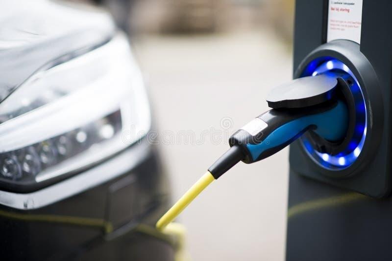 Elektroauto, das in einem öffentlichen Bereich, teilweise Ansicht des Autos auflädt lizenzfreie stockbilder