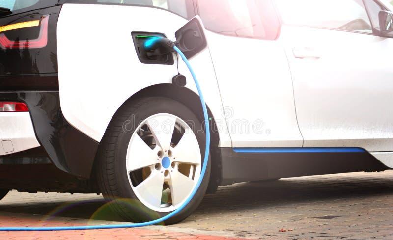 Elektroauto, das mit einem Ladegerätsockel auflädt stockfotografie