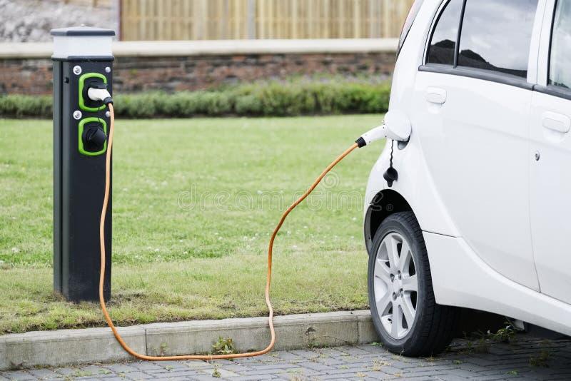 Elektroauto, das mit Kabel- und Fahrzeuggebührenpunkt am carpark auflädt lizenzfreie stockfotografie