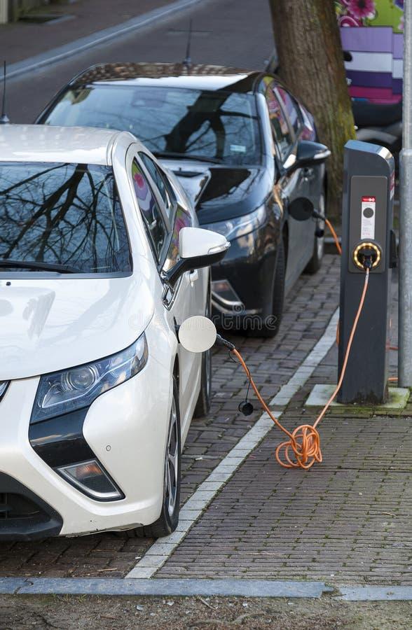 Elektroautos angeschlossen für die Aufladung lizenzfreie stockbilder