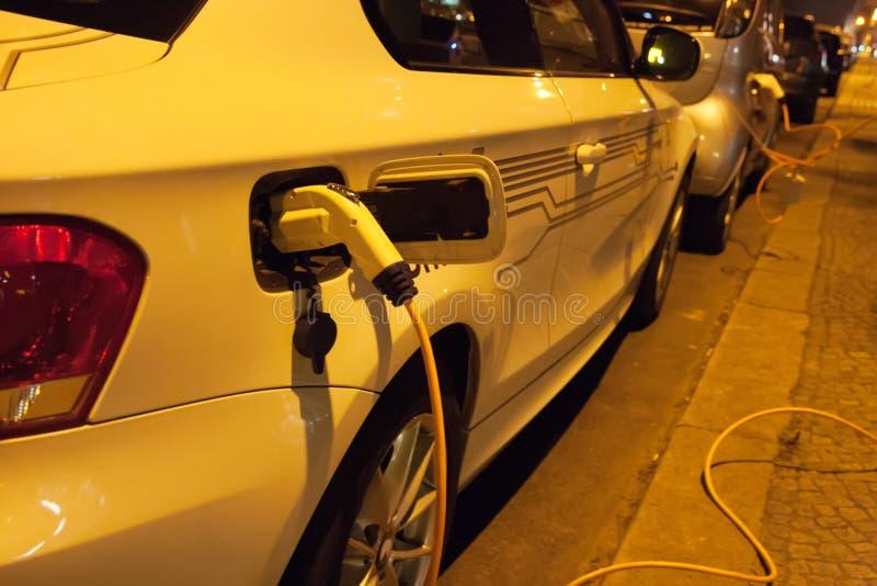 Elektroautos, die nachts in der Stadtstraße aufladen stockfoto