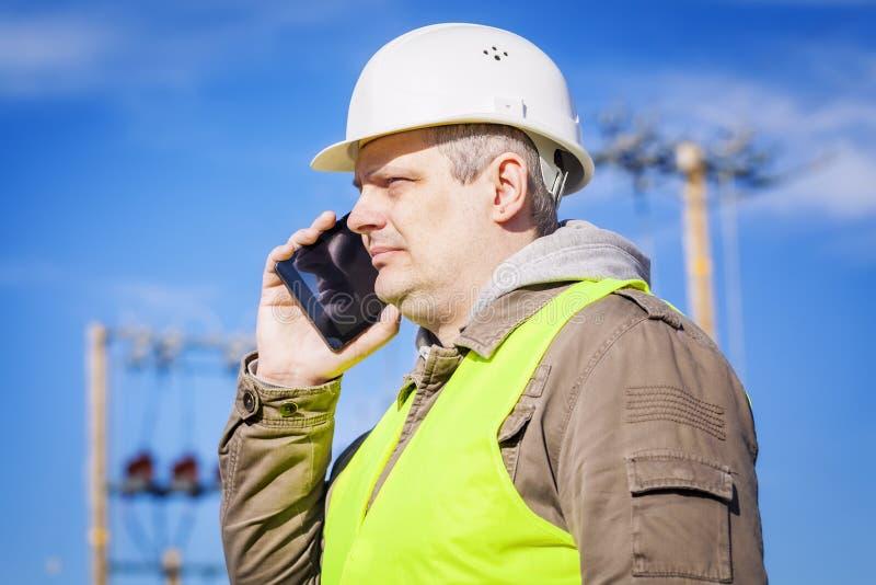 Elektroingenieur, der am Handy an draußen spricht lizenzfreies stockbild