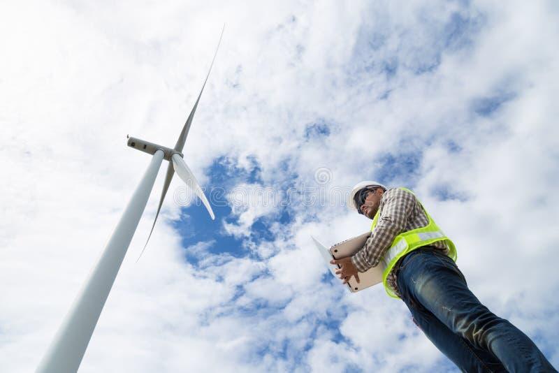 Elektroingenieure, die am Windkraftanlagestromgenerator arbeiten stockfotografie