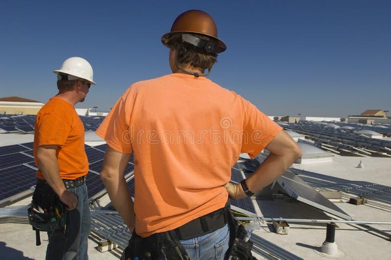 Elektroingenjörer på solenergiväxten arkivfoto