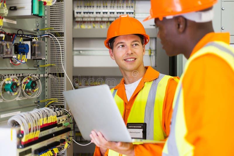 Elektroingenjörer som justerar transformatorn arkivfoton