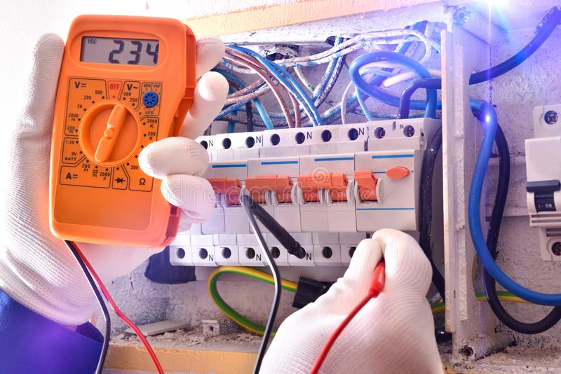 Elektroinstallateur met beschermende elementen die elektrometingen dicht omhoog maken stock fotografie