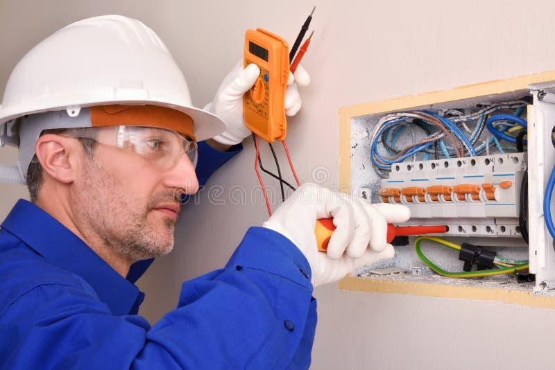 Elektroinstallateurshuisvesting die in een elektropaneel van huis werken royalty-vrije stock foto