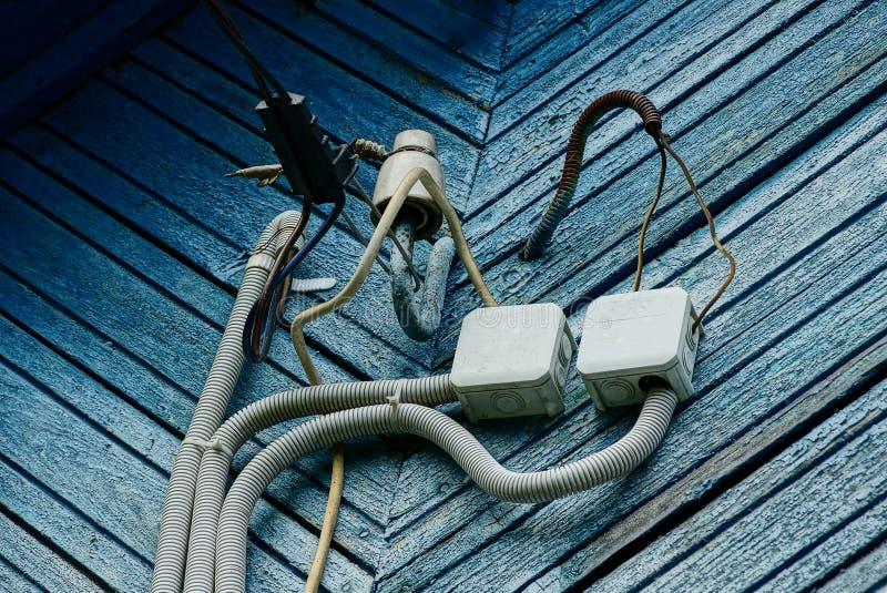Elektrokabeldraden en dozen op een blauwe houten muur royalty-vrije stock afbeeldingen