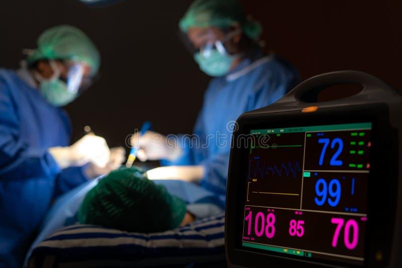 Elektrokardiogram w szpitalnej operaci operacyjnej izbie pogotowia pokazuje cierpliwego t?tno z plamy dru?yn? chirurdzy w tle obrazy stock