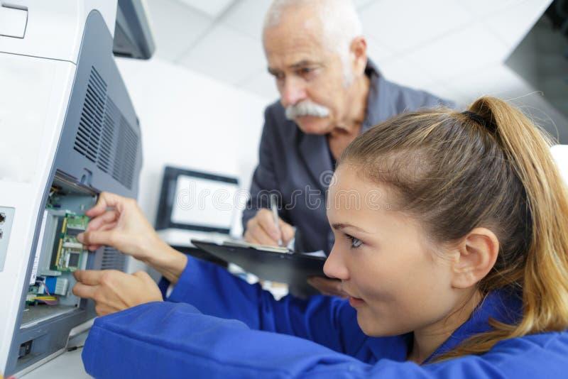 Elektromekanisk tekniker som reparerar anordningen royaltyfria foton