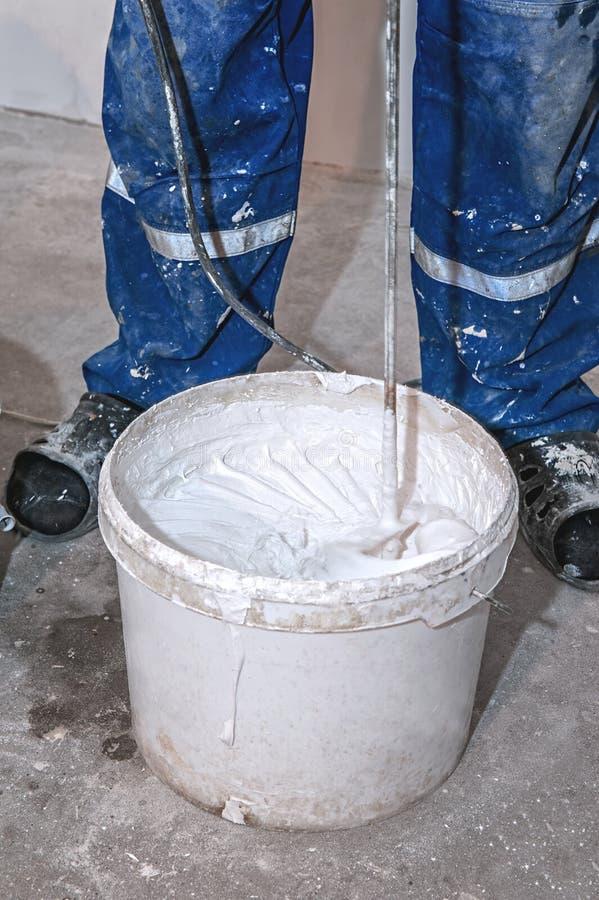 Elektromixer mischt Farbe in einem weißen Eimer Schaufelmischer über einem Eimer weißer Farbe für die Wand, die Werkzeuge und die lizenzfreies stockbild