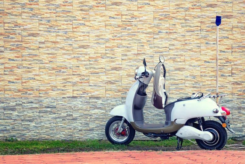 Elektromotorroller parkte nahe einer schönen Wand für die Aufladung lizenzfreies stockbild